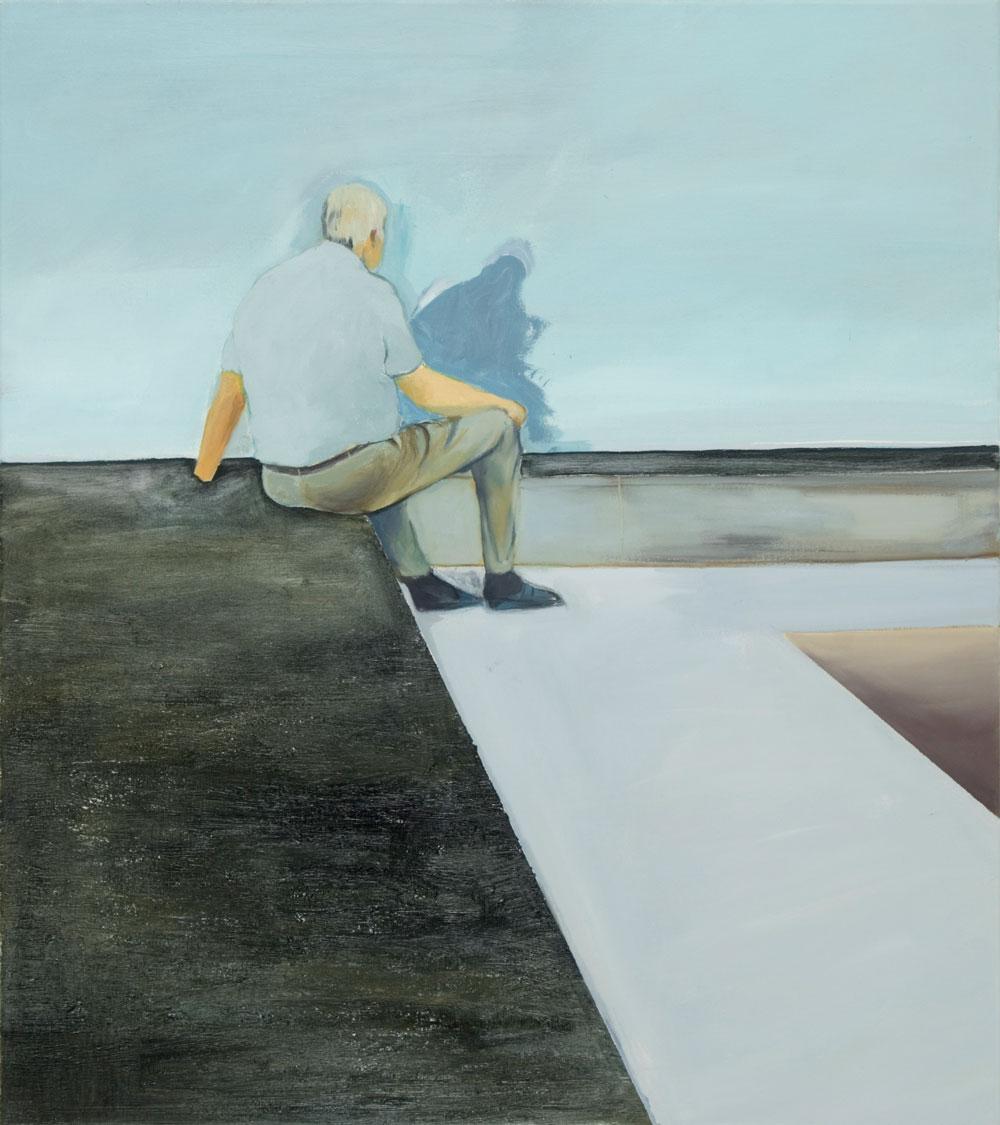 ein alter Mann in graune Hemd sitzt vor einer grauen Wand