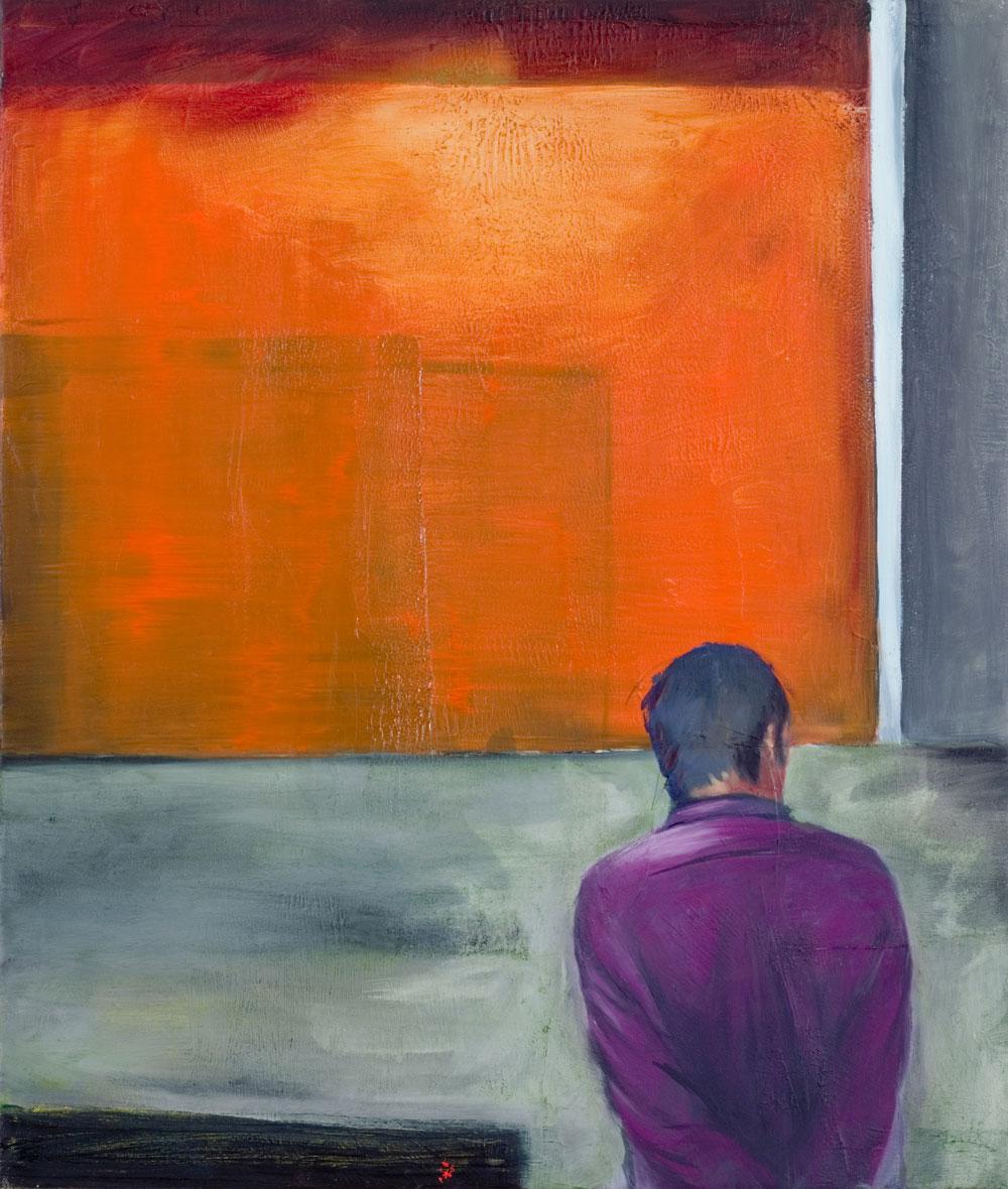 Ein Mann mit lila Hemd steht vor orangefarbener Wand die oben leuchtet