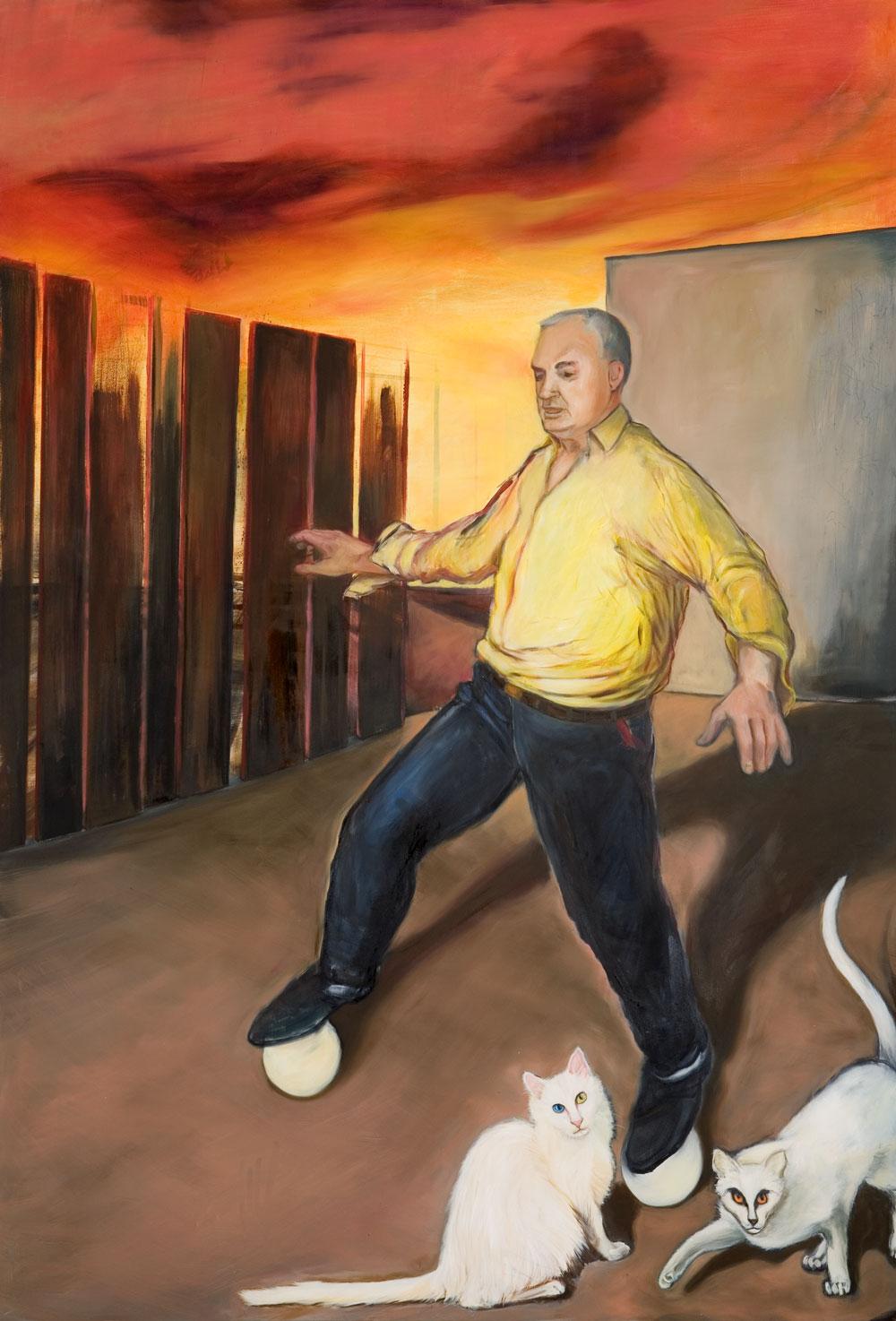 Mann in schwarzen Hosen und gelbem Hemd balanciert auf zwei Bälllen während zwei weisse Katzen um seine Beine streichen